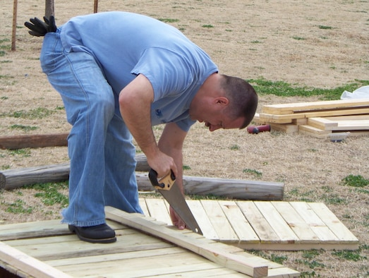 Master Sgt. Bruce Faris, 964th Airborne Air Control Squadron, works to construct a fence around the Moore Community Garden March 7.