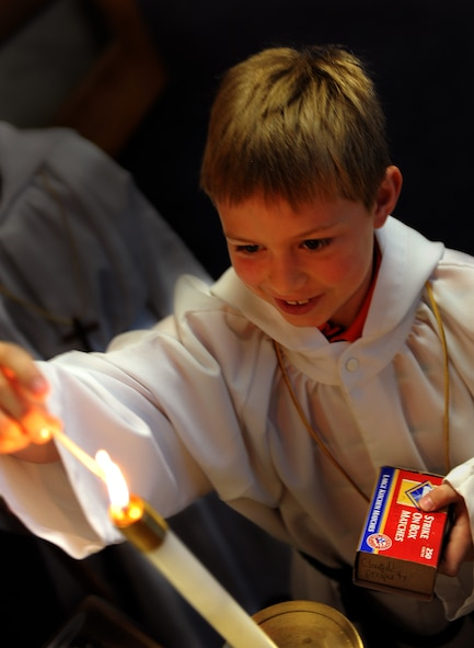 MOUNTAIN HOME AIR FORCE BASE, Idaho -- Bridger Beaty, an altar boy, lights a candle during Sunday morning mass at Liberty Chapel Feb. 22. The base chapel offers counseling as well as religious services to Gunfighters and their families. (U.S. Air Force photo/ Airman 1st Class Ashley Tank)
