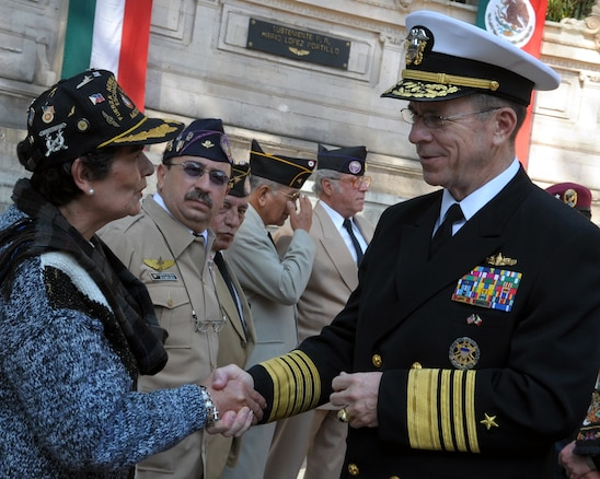 U.S. Navy Adm. Mike Mullen, chairman of the Joint Chiefs of Staff, talks to the spouse of a former 201st Fighter Squadron member at Chapultepec Park in Mexico City, Mexico, March 6, 2009.