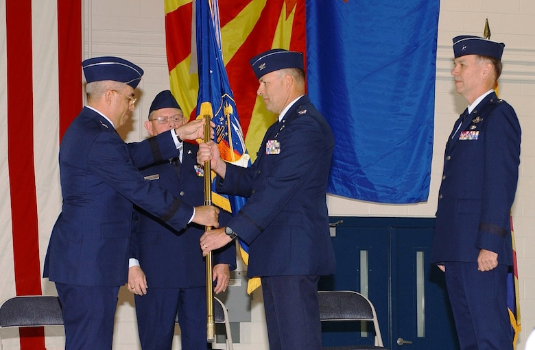 Col. Greg Stroud (center) assumes command of the 162nd Fighter Wing with a symbolic passing of the flag from Brig. Gen. Michael Colangelo, Arizona Air National Guard commander, March 7. The former 162nd commander, Maj. Gen. Rick Moisio (right), pinned on his second star at the conclusion of the ceremony and will move to his next post as the deputy director of the Air National Guard. (Air National Guard photo by Staff Sgt. Sarah Elliott)
