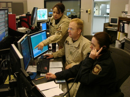 Air & Marine Operations Center director Tony Crowder (center) is assisted by