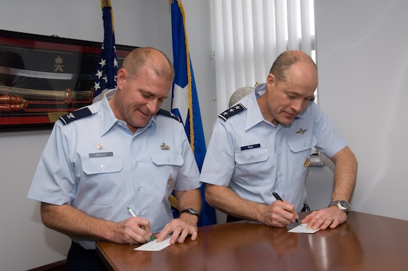 Lt. Gen. Allen G. Peck (right), commander of Air University, and Col. Kris D. Beasley, commander of the 42nd Air Base Wing, sign their pledge cards for the 2009 Air Force Assistance Fund campaign in the general's office March 9. According to project officer Capt. Benjamin Henley, a goal of $72,031 has been set for Maxwell-Gunter in the campaign ending April 5. The fund benefits organizations that help Air Force people with aid in an emergency, with educational needs, or to have a secure retirement home for Air Force widows or widowers. Active-duty Airmen and retirees may elect payroll deductions, but cash and money orders are also accepted. (Air Force photo by Melanie Rodgers Cox)