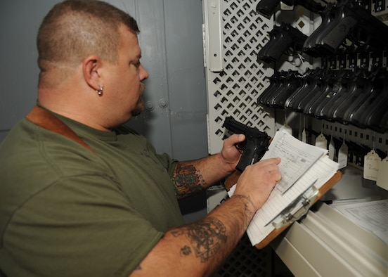 SCOTT AIR FORCE BASE, Ill. --Rod Hampton, War Readiness Element material coordinator, inspects a M-9 Berettas for the proper serial number before issuing to a customer. (U.S. Air Force photo/Staff Sgt. Paul Villanueva)