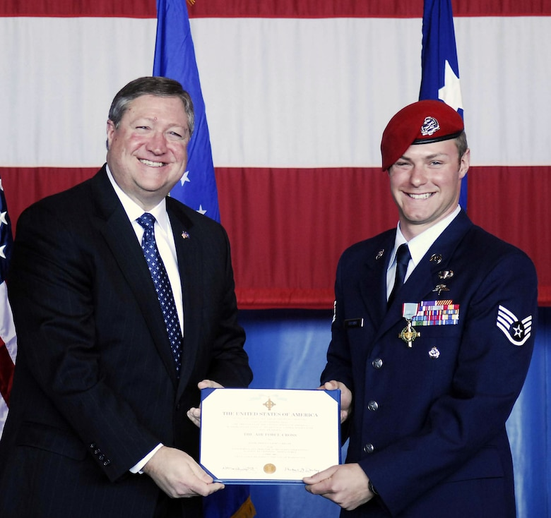 Secretary of the Air Force Michael B. Donley presents Staff Sgt. Zachary Rhyner the Air Force Cross March 10 at Pope Air Force Base, N.C. Sergeant Rhyner of the 21st Special Tactics Squadron received the medal for uncommon valor during Operation Enduring Freedom for his actions during an intense 6.5-hour battle in Shok Valley, Afghanistan, April 6, 2008.  (U.S. Air Force photo)