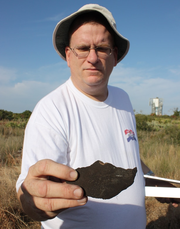 Thomas Penders of the 45th Civil Engineer Squadron holds a piece of ancient pottery uncovered at the Little Midden site at Cape Canaveral Feb. 27. (U.S. Air Force photo/Airman 1st Class David Dobrydney)