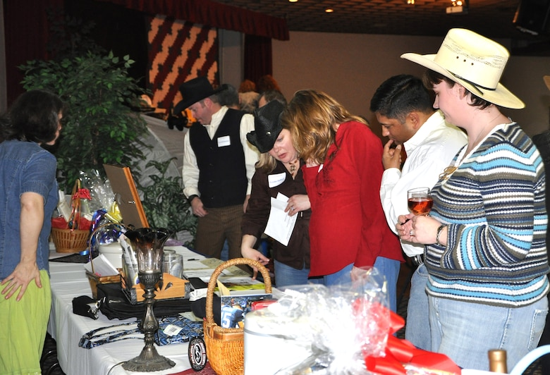 Participants at an Officers Spouses auction browse the tables full of items to be auctioned at Club Fairchild Mar. 6. Items auctioned off for the evening ranged from a complete set of camping gear to a luxurious spa getaway and an abundance of other items that were auctioned off for varying prices.  With various closing times on the auction tables, there was a frenzied rush seconds before closing for those ensuring they had bid the highest. (U.S. Air Force photo/Senior Airman Jocelyn Ford) Patty