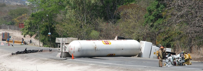 SOTO CANO AIR BASE, Honduras - Firefighters from Comayagua and Joint Task Force-Bravo set up a water hose to cool an overturned fuel tanker on C.A. 5 approximately 8 kilometers north of the base Friday.  The tanker overturned after hitting a horse around 8 a.m. and caused traffic to be halted in both directions for more than 24 hours.  (U.S. Air Force photo/Tech. Sgt. Rebecca Danét)