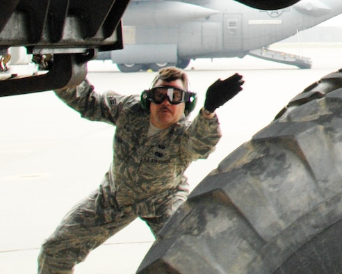 """Senior Airman Michael Boehm, a member of the 32nd Aerial Port Squadron, guides a HUMVEE out of a C-130 aircraft in the """"Engines Running Off/On Load"""" exercise during the 22nd Air Force Aerial Port ROUNDUP, a first-of-its-kind event for Reserve aerial port members in 22nd Air Force. (U.S. Air Force photo/1st Lt. J. Justin Pearce)"""