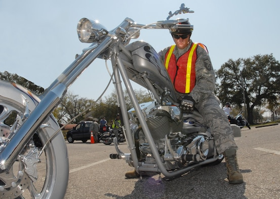 Master Sgt. Chad Wilkey, 96th Logistics Readiness Squadron, adjusts his 'award-winning' custom chopper before the group ride at the Team Eglin Motorcycle Safety Day March 13 at Eglin Air Force Base, Fla. The second annual event brought out approximately 280 riders to participate in safety discussions, riding skills competition and group ride. (Air Force illustration/Samuel King Jr.)