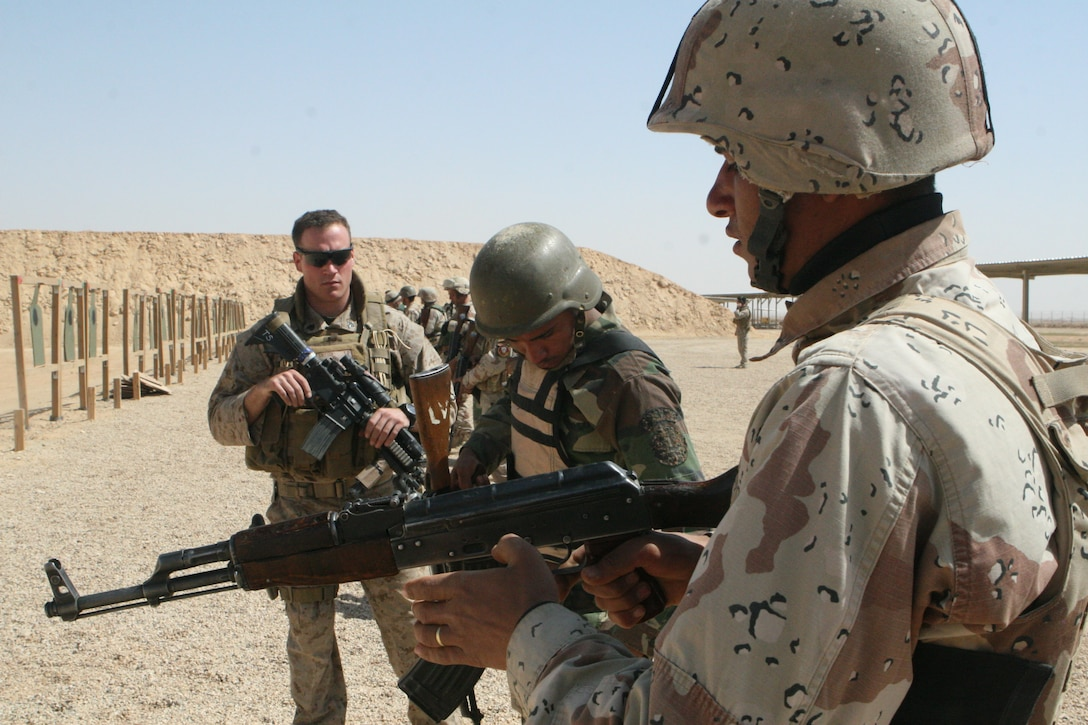 A Marine instructor from 2nd Platoon, Company B, 1st Reconnaissance Battalion, Regimental Combat Team 8, observes Iraqi Commandos from the 7th Iraqi Army, loading their weapons and preparing to fire, March 20, 2009.  The live-fire exercise concluded the six-day weapons training exercise the Commandos conducted with RCT-8's 2nd Recon Platoon.