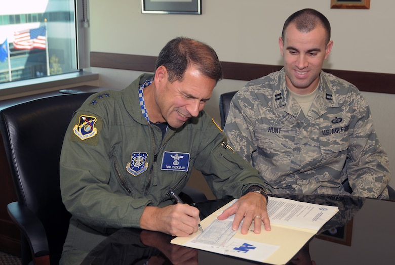 SMC Commander Lt. Gen. Tom Sheridan signs a pledge form for this year's Air Force Assistance Fund Campaign as Capt. Shaun Hunt looks on. This year's campaign runs March 9 through April 17. Airmen can donate through their individual unit representatives. (Photo by Joe Juarez)