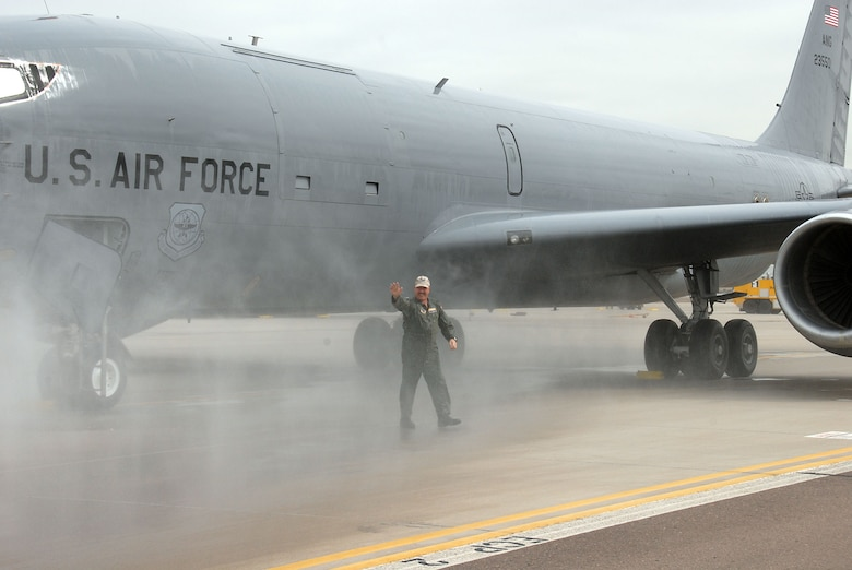 Col. William E. Anderson waves hello after getting doused with a fire hose upon returning from his final flight as outgoing commander of the 161st ARW.