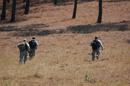 U.S. Army Soldiers run to the treeline after a simulated helicopter crash during an exercise near La Paz, Honduras, March 20. Eighteen members of the 1st Battalion, 228th Aviation Regiment, assigned to Joint Task Force-Bravo here, took part in the day-long training exercise. The training sharpened land navigation, communication equipment, and aircraft vectoring skills. (U.S. Air Force photo/Tech. Sgt. Mike Hammond)
