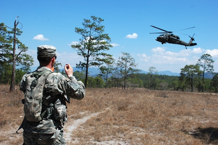U.S. Army Specialist James Ferguson signals to a HH-60 Blackhawk helicopter as it prepares to land and extract aircrew members during an exercise near La Paz, Honduras, March 20. Eighteen members of the 1st Battalion, 228th Aviation Regiment, assigned to Joint Task Force-Bravo here, took part in the day-long training exercise. The training sharpened land navigation, communication equipment, and aircraft vectoring skills. (U.S. Air Force photo/Tech. Sgt. Mike Hammond)