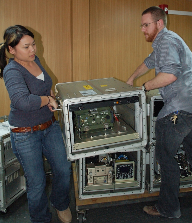 "Andrina Luczon and Keith Lareau break down a Roll-On-Beyond-Line-Of-Sight Enhancement System ""B-kit"" after diagnosing a problem with the unit March 12 at Manas Air Base, Kyrgyzstan. Both contractors are deployed to Manas AB from San Diego to train KC-135 Stratotanker aircrews on how to use and troubleshoot the system, as well as work through technical and procedural challenges with the system. Ms. Luczon and Mr. Lareau are Northrop Grumman contractors. (U.S. Air Force photo/Maj. Damien Pickart)"