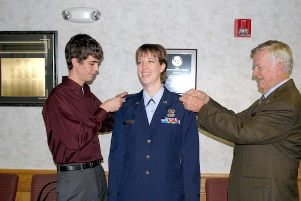 First Lieutenant Jacquelyn Stauffer, an Operations Officer with the 507th Air Refueling Wing's Logistics Readiness Squadron beams as she is promoted during a pin-on ceremony.  Assisting in pinning on her silver bars are her brother Daniel Stauffer and grandfather Major Geneneral (USAF Ret.) Chris Adams.