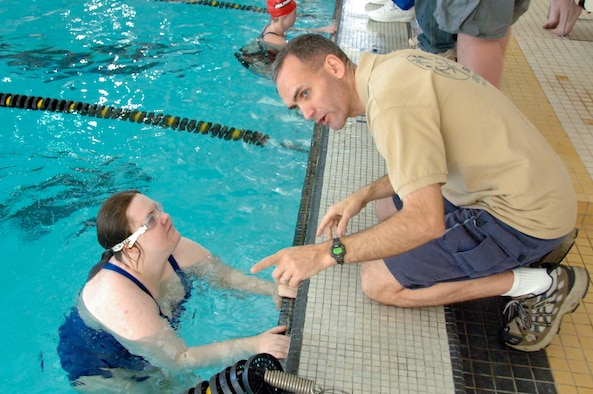 Special Olympics swimmer Tiffany Capistran, of the Montgomery Blue Marlins team, gets words of advice from Chap. (Maj.) Kleet Barclay during a swim meet at Alabama State University March 13. The staff of Gunter's Enlisted Heritage Research Institute, the Holm and Barnes Centers and the 42nd Air Base Wing volunteered their assistance for the event, which in addition to the Blue Marlins, drew swimming teams from Dothan, Mobile, Gadsden and Tuscaloosa, Ala. (U.S. Air Force photo by Donna L. Burnett)