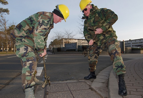 Staff Sgt. Stephen Sether (left) and Master Sgt. Richard Dumire of the 210th Engineering and Installation Squadron from the Minnesota Air National Guard move a manhole cover to gain access to conduits on Ramstein Air Base, Germany on March 2, 2009. The 210th EIS deployed about thirty Airmen to install communications cables to the base in early 2009. USAF Official photo by Technical Sgt. Erik Gudmundson.