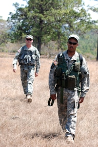 U.S. Army Chief Warrant Officer Timothy Forrestal and Army Spc. James Ferguson hike across a clearing during the final leg of their team's trek March 20 in the wooded area near La Paz, Honduras. The aircrew members were part of five teams of aviators practicing land navigation, ground-to-air communication, and extraction procedures during an exercise conducted by Alpha Company, 1st Battalion, 228th Aviation Regiment assigned to Joint Task Force-Bravo at Soto Cano Air Base, Honduras. (U.S. Air Force photo/Tech. Sgt. Mike Hammond)