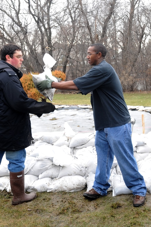 Staff Sgt. Nathaniel Newkirk, 319th Operations Support Squadron, hands off a sandbag to another volunteer while helping with flood preparations in a Fargo, N.D., neighborhood. Sergeant Newkirk is one of more than 100 Warriors of the North who have volunteered in the effort to mitigate flood damage in the Red River Valley to date. (U.S. Air Force photo/Tech. Sgt. Amanda Callahan)