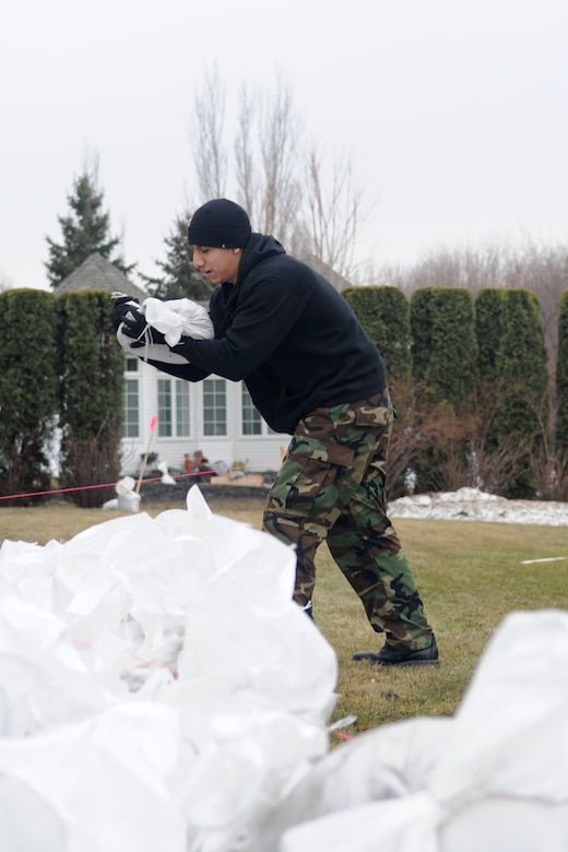 Airman 1st Class Emiliano Rivera, 319th Operations Support Squadron, helps create a sandbag wall through a neighborhood in Fargo, N.D. Airman Rivera is one of many volunteers from Grand Forks Air Force Base who are aiding in flood prevention efforts throughout the Red River Valley. (U.S. Air Force photo/Tech. Sgt. Amanda Callahan)