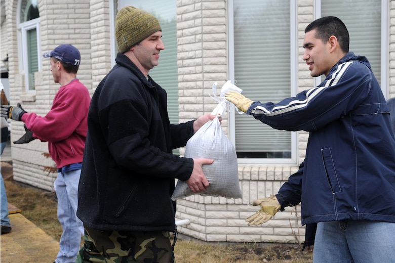 Tech. Sgt. Yancey Callahan (left) and Senior Airman Isaac Zavala, both of the 319th Operations Support Squadron, are part of a human sandbag chain comprised of neighbors and volunteers in Fargo, N.D. Warriors of the North are supporting the flood preparation efforts by volunteering at many locations throughout the Red River Valley. (U.S. Air Force photo/Tech. Sgt. Amanda Callahan)