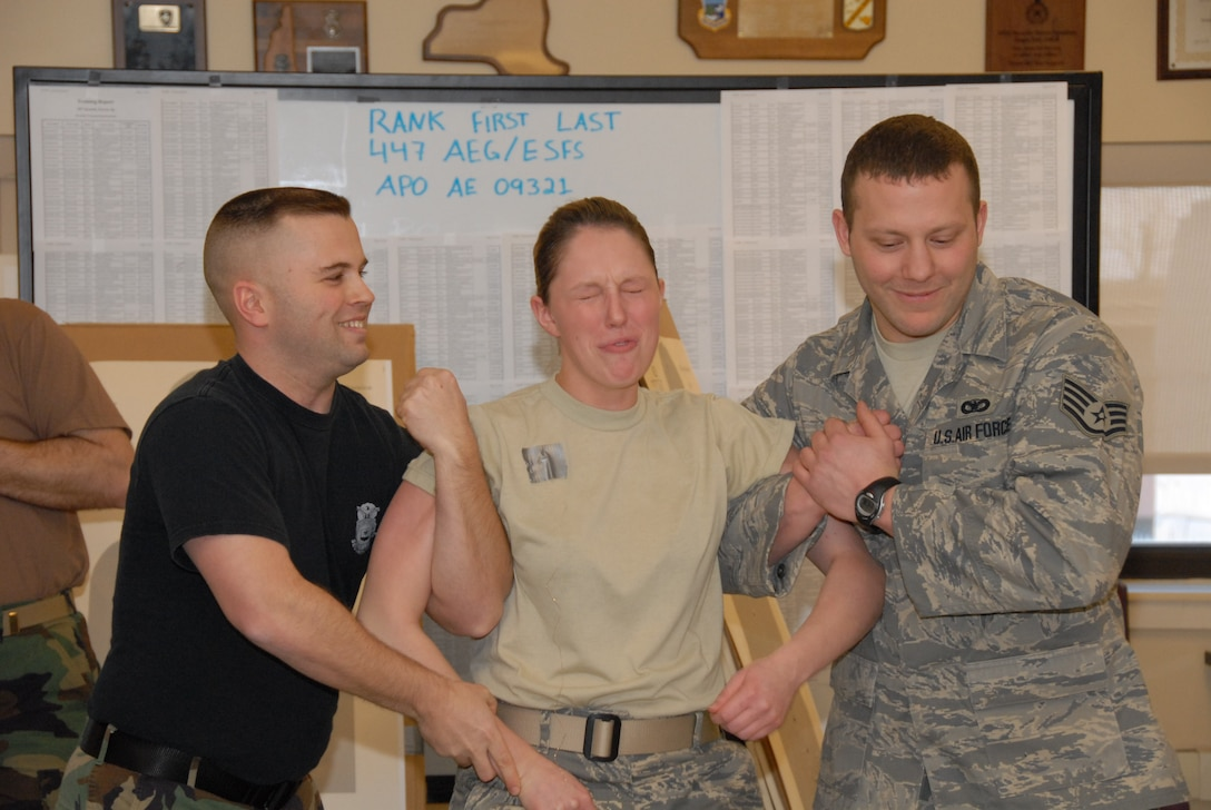 Senior Airman Michael Dennee on left and Staff Sgt. Tommy Rodgers on right seem to find joy in the pain that Airman 1st Class Cassidy Milliman is receiving. In order to fully qualify on the X26 Taser, members had to experience firsthand the incapacitation delivered by the 50,000 volts penetrating their body.
