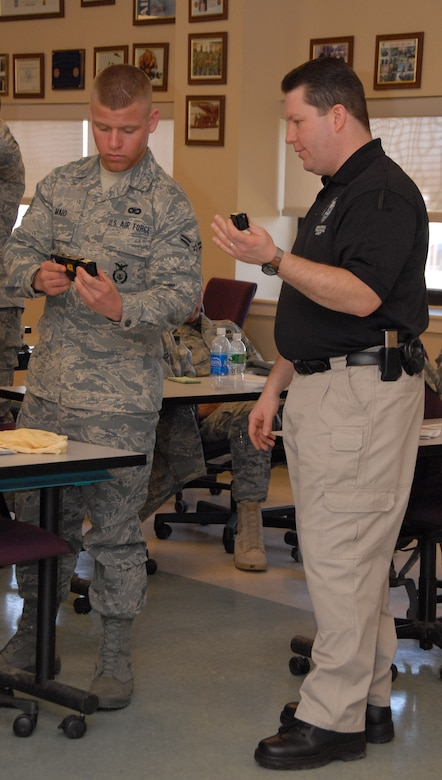 Officer Tom Licata, Niagara Falls Police Department Firearms Instructor, schools Airman 1st Class Michael Maio on the proper use of the X26 Taser. During a daylong class, 107 AW Security Force Members learned the techniques necessary to safely immobilize an evil doer using an electronic control device aka Taser.