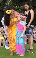 A member of the Hale Koa Hotel luau cast demonstrates different ways to wear a sarong on a luau guest.