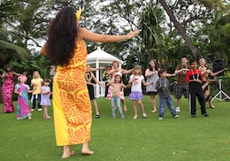 Michelle Kama, producer of the Hale Koa Hotel luau show, shows guests how to do the hula. During the four-hour evening, guests can experience the Polynesian culture interactively through food, dancing and crafts.