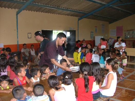 FORWARD OPERATING LOCATION MANTA, Ecuador -- Chaplain (Capt.) Gabriel Rios, deployed to FOL Manta from Spangdahlem Air Base, Germany, serves lunch to children at the Jesus de Nazareth community kitchen in Manta, Ecuador Feb. 27. A good portion of the chaplain's work involves building partnerships with local organizations to make a lasting impact on the community outside the gates. (U.S. Air Force photo)