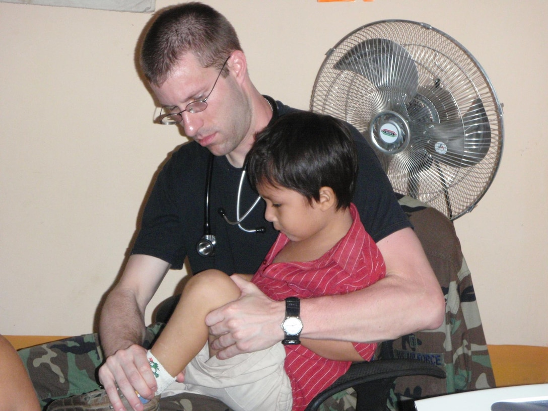 LORETO REGION, Peru -- Capt. (Dr) Wilmont Martin examines a pediatric patient during a medical mission to Peru March 12.  A team of 15 Air Force doctors and technicians, along with more than 50 Peruvian Navy, Ministry of Health, and civilian practitioners, treated patients in the remote region for two weeks as part of the ongoing Riverine Project, a three year humanitarian medical project sponsored by Twelfth Air Force (Air Forces Southern).  (U.S. Air Force photo by Master Sgt. Jesse Moreno)
