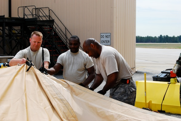 DOBBINS AIR RESERVE BASE, Ga. - From left to right, Lt. Col. John Hayes, 22nd Air Force services director, receives training on how to set up a single pallet expeditionary kitchen from combat services training instructors Tech Sgts. John Joyner and Jovor Dungee. The instructors conducted field training to Reserve Services units on preparing and providing meals during the 22nd Air Force Aerial Port ROUNDUP, March 13-15, here. (U.S. Air Force photo/Staff Sgt. Steve Lewis)