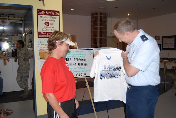"Col. John Gordy, 43rd Airlift Wing Vice Commander, presents the Harley Pope coin, the Pride in Excellence coin and a ""Popetastic"" T-shirt to Sharla Alexander at the Fitness Center Monday. Ms. Alexander was given the coins as thanks for her 23 years of service as the Fitness Center Director. (U.S. Air Force Photo by Tech. Sgt. Todd Wivell)"