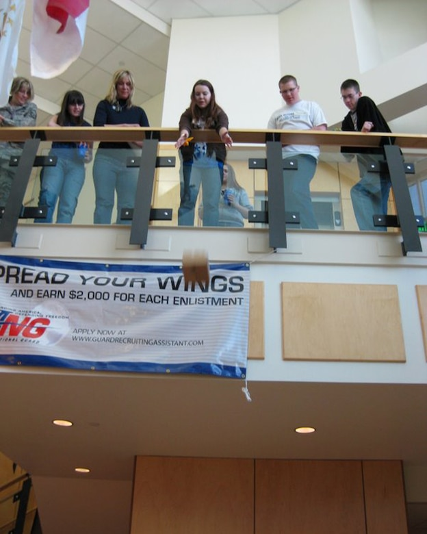"""Master Sgt. Sandee Eisert, Katie Scoresby, Debbie Ramsay, Kyler Brunsen and Jeff Reading watch as Nevin Dewitt drops """"Humpty Dumpty"""" to a target below.  The activity was part of a team building exercise as eight teens from around the state met at the Utah Air National Guard base to learn more about their roles as the first """"Speak Out for Military Kids"""" team in the state.  SOMK is a youth-led, adult-sponsored program created to help educate communities about military deployment issues and the effect it has on military families.  Each teen has experienced either a mom or dad being deployed and knows first-hand how kids struggle while a parent is away serving their country.Courtesy photo."""