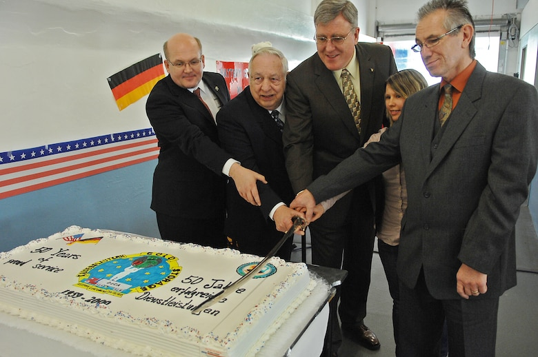 Terry Batenhorst, DeCA Europe director of operations, Austin Romesburg, Kaiserslautern Cold Storage(KCS) chief, Thomas E. Milks, DeCA Europe director, and KCS newest and longest employed members (left to right) cut the cake during a ceremony celebrating KCS's 50th anniversary, Ramstein Air Base, Germany, March 20, 2009. (U.S. Air Force photo by Airman 1st Class Tony R. Ritter)