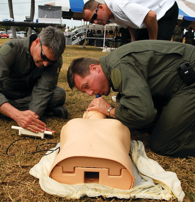 Colonel Gary L. Akins, 201 AS commander, performs rescue breathing on a CPR dummy, while Col. Kurt Vogel, National Guard Bureau AF/A8 advisor, looks at the monitor to ensure Colonel Akins is giving the correct amount of breath. (U.S. Air Force photo/ Tech. Sgt. Adrianne Wilson)