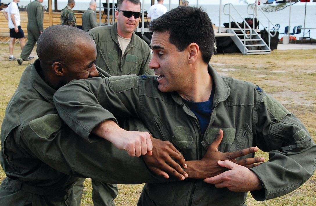 Technical Sgt. Phil Taylor, 201 AS flight attendant, and Col. Marc Sasseville, 113th Wing vice commander, practice hand-to-hand combat training March 14. The 113th Security Forces Squadron Ravens taught the hand-to-hand combat. (U.S. Air Force photo/ Tech. Sgt. Adrianne Wilson)