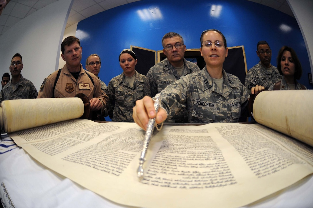 JOINT BASE BALAD, Iraq -- Chaplain (Capt.) Sarah Schechter, 332nd Air Expeditionary Wing rabbi, describes the newly arrived Jewish Torah following a Torah dedication ceremony at Gilbert Memorial Chapel here March 21. A Torah is a big parchment leather scroll on which the Five Books of Moses are handwritten in Hebrew. For thousands of years, this is how Jews have maintained their law, teachings, religion and society. (U.S. Air Force photo/Senior Airman Elizabeth Rissmiller)