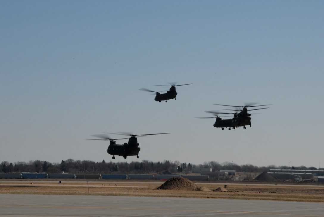 Four Chinooks, from Fort Riley, Kansas, take off from Joe Foss field, Sioux Falls, S.D. after landing for fuel and food. The crews took off loaded with troops and equipment headed for the devastated areas in North Dakota affected by severe flooding.