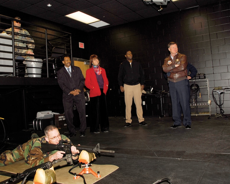 Capt. Joe Hardin, 114th Security Forces commander, demonstrates his marksmanship skills in the Firearms Training Simulator room during a tour by Suriname Defense Minister Ivan Fernald and U.S. Ambassador Lisa Bobbie Schreiber Hughes. Defense Minister Fernald and Ambassador Schreiber Hughes were in South Dakota for a tour of the state as part of the Growth through Partnership program.