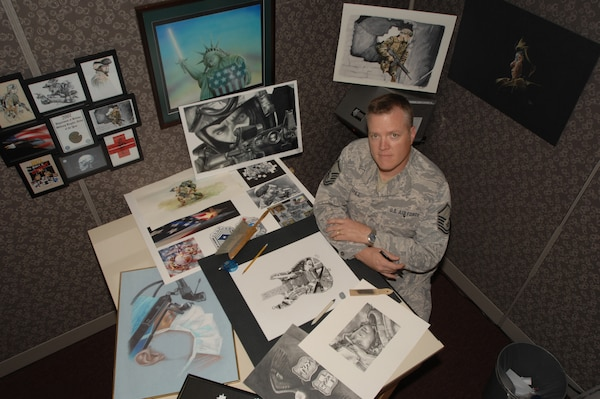 """Master Sgt. William """"Cody"""" Vance sits surrounded by his art, much of it award-winning.  Sergeant Vance, assigned to the 59th Medical Wing Medical Multimedia Center, is the recipient of the 2008 Military Graphic Artist of the Year for the second time in a row.  He is the last Senior Noncommissioned Officer in the Air Force's graphic arts career field. (U.S. Air Force photo/Senior Airman Robert Barnett)"""