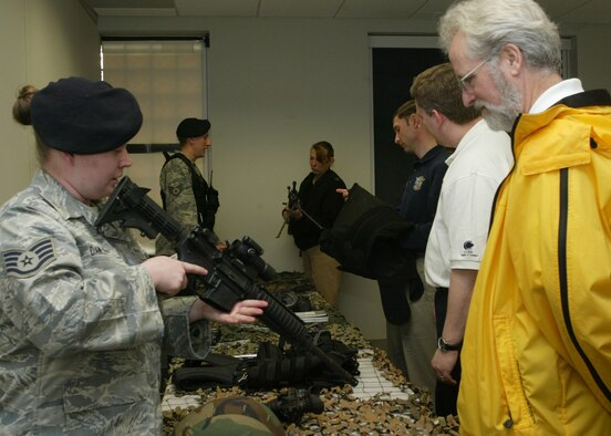 Dobbins Air Reserve Base, Ga. - Staff Sgts.  Jennifer Dawley and Richard Potter, 94th Security Forces Squadron response force members, give members of the 2009 Honorary Commanders Association (HCA) an up close and personal look at the weapons used by security forces for base security during a tour on March 24.  The HCA is a cooperative effort of the Cobb Chamber of Commerce, Dobbins Air Reserve Base and Naval Air Station Atlanta (NAS).  Civilian business, government service employees and educators are paired with commanders and senior officers of military units stationed at Dobbins and NAS.  (U.S. Air Force photo/Don Peek)