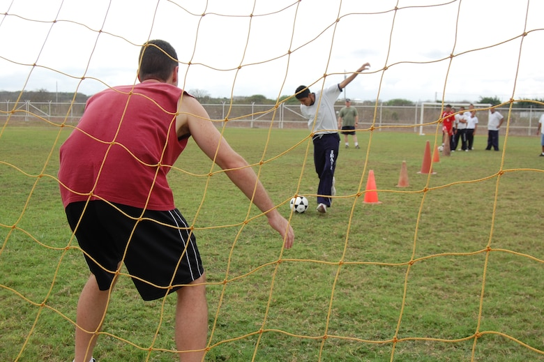 Maj. Chris Shea (far left), 478th Expeditionary Operations Squadron assistant director of operations, defends a soccer goal during a sports day here with students from Manta, Ecuador's Angelica Flores special needs school April 25. FOL Manta hosted the all-day event to teach 40 students American sports and build their teamwork and confidence. (U.S. Air Force photo by 1st Lt. Beth Woodward)