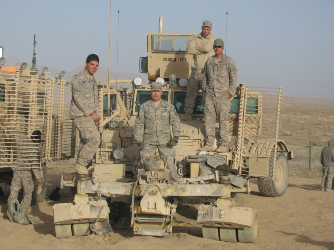 Senior Master Sgt. Kevin McRae stands with the mine roller and the crew after the truck was struck by an IED. Sergeant McRae traveled with the Route Clearance Package from the Kentucky National Guard as on scene support element. (Air Force photo)