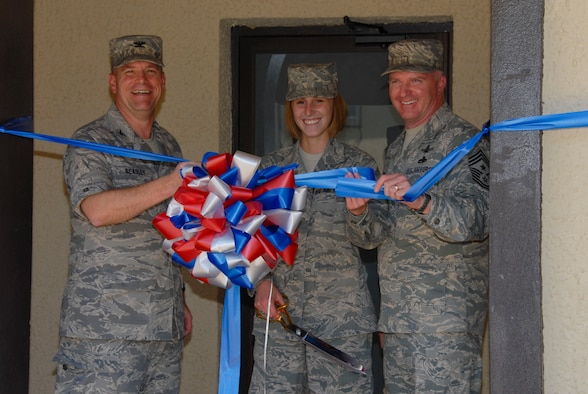 Airman Basic Lindsey Minnicker of Air University Education Logistics and Communications gets ready to cut the ribbon for the opening of the remodeled Stripes Lounge April 24. Looking on from left are 42nd Air Base Wing Commander Kris D. Beasley and Chief Master Sgt. Mark Repp, 42nd ABW command chief. The enlisted club at Maxwell, the Stripes Lounge has a new entrance on White Avenue with custom awnings, new flooring and furniture, a refinished bar area, different seating group areas, a fireplace, and updated paint scheme.  The lounge had been closed for about four months.