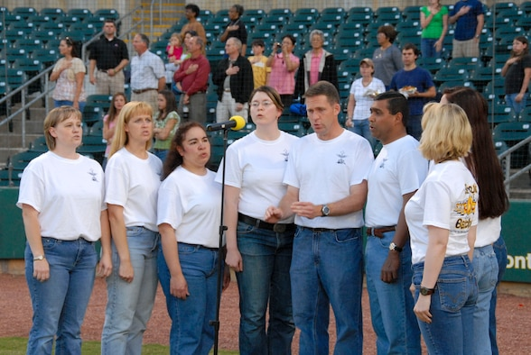 On the Montgomery Biscuits minor league baseball team's first military discount night, April 22, at Riverfront Stadium, students from Air Command and Staff College had the opportunity to participate with opening festivities.  Shown singing the national anthem from left are Maj. Niki Kissiar, Maj. Ericka Flanigan, Maj. Estrella Rodgers, Maj. Melinda Moreau, Maj. David Hood, Group Capt. Andrew Wijesuriya of the Sri Lanka Air Force, Juanita Jasper, Maj. Ila Hahn, and Navy Lt. Cmdr. Shannon Callahan.  Throwing out the first pitches were dependents Greg Ogorek Jr., age 11, and Maddie Arnold, age 9. (U.S. Air Force photo by Jamie Pitcher)
