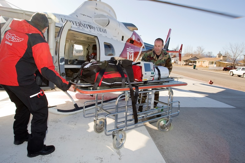 Vernal, Utah ? Staff Sgt. Alan Reynolds of the 151st Medical Group helps air paramedic Tom Robertson unload equipment from a Bell 430 AirMed helicopter into the Vernal hospital.  Sergeant Reynolds is one of 19 Utah Air Guard medics who are participating in a special ride-along program with the University of Utah AirMed unit.  The ride-along program is designed for local third-year medical residents, Emergency Medical Technicians, firefighters and other emergency response personnel so they can observe the critical-care air transport process.   U.S. Air Force photo by Tech. Sgt. Michael D. Evans.