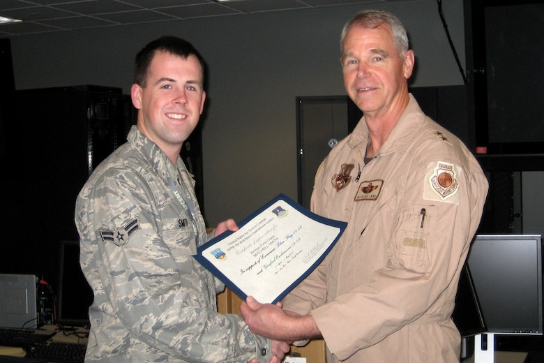 Airman 1st Class Mitchell Smith, combat reports technician, 103rd Air Operations Group, receives a certificate of appreciation from Major General William L. Holland, Deputy Commander, U.S. Air Forces Central, Shaw Air Force Base, S.C. for his contributions to Exercise Blue Flag.  (U.S. Air Force File Photo)