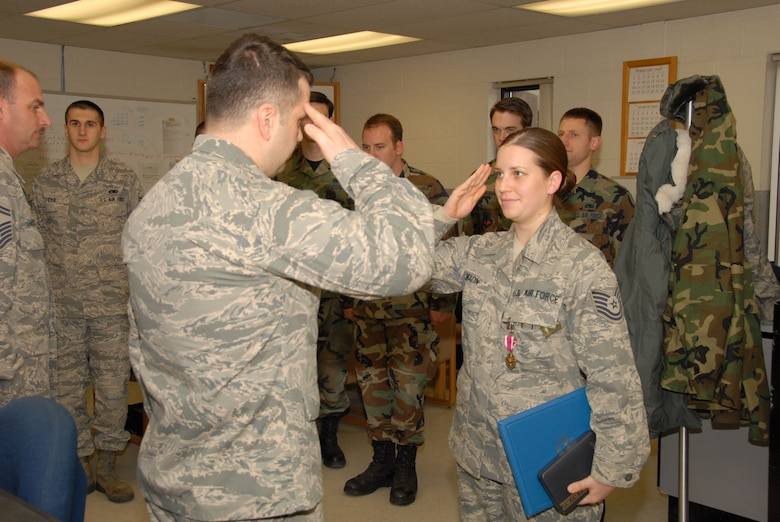 Tech. Sgt. Carey Malin, avionics specialist, 103rd Avionics Flight, salutes Maj. Wayne B. Ferris, maintenance squadron commander, 103rd Maintenance Squadron, after receiving her Meritorious Service Medal during a ceremony on base April 5th, 2009.  Malin was awarded the medal for her contributions to the honor guard.  (U.S. Air Force photo by Staff Sgt. Erin McNamara)
